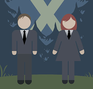 A man and a woman wearing suits, in the woods with trees and two spotlights crossing in the sky