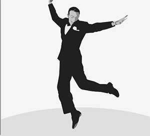 A man dancing or jumping around in a black tux.